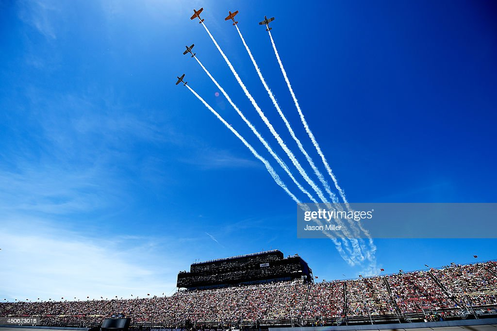 Five T-34's from Hooligan's Flight Team perform a flyover prior to the NASCAR Sprint Cup Series Quicken Loans 400 at Michigan International Speedway on June 15, 2014 in Brooklyn, Michigan.