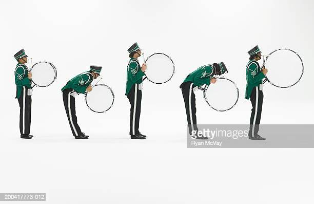 Five teenagers (14-18) in band uniforms carrying bass drums, side view