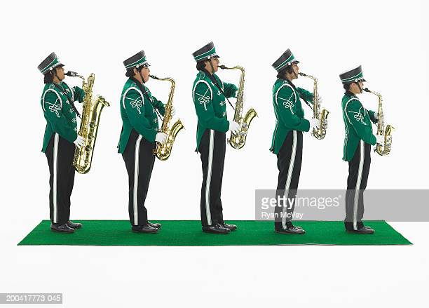Five teenagers (15-17) in marching band uniforms holding saxophones