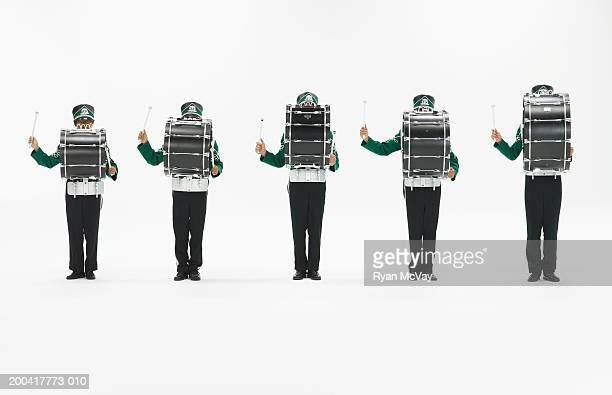 Five teenagers (14-18) in marching band uniforms playing bass drums