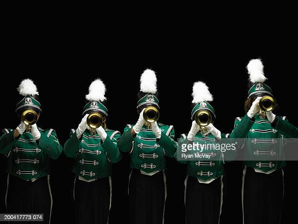 Five teenagers (14-18) in marching band uniforms playing trumpets