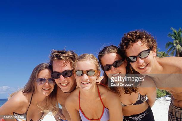 Five teenagers (16-17) smiling at camera on beach, portrait