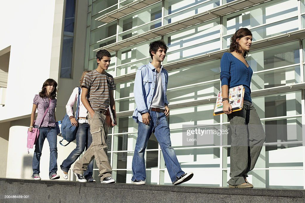 Five teenagers (13-17) walking in line along wall outside building : Stock Photo