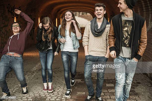 Five teenagers walking through tunnel laughing and joking