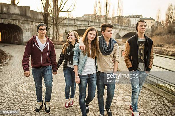 Five teenagers walking together beside river