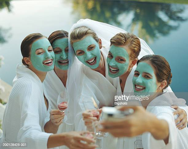 Five women in cosmetic face masks, one woman wearing bridal veil