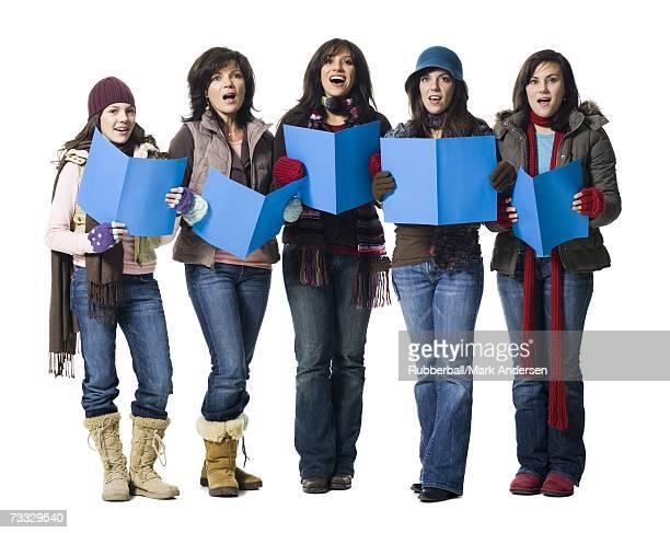Five women in winter coats singing with sheet music