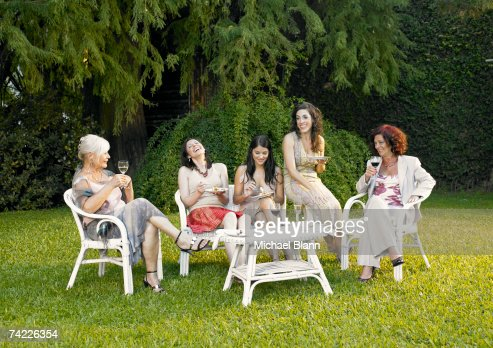 'Five women relaxing in garden, drinking wine' : Foto de stock