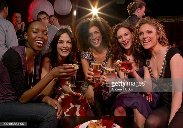 Five women sitting with drinks at table in club, smiling, portrait