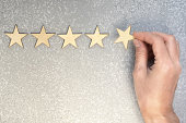 five wooden stars and hand putting the last one to increase rating on a silver background, top view with copy space
