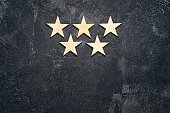 Five wooden stars arranged in two rows, 3 on the top and 2 below, on a dark cement background with copy of the space. Concept of service rating and quality of trade. Top view, copy space for your text