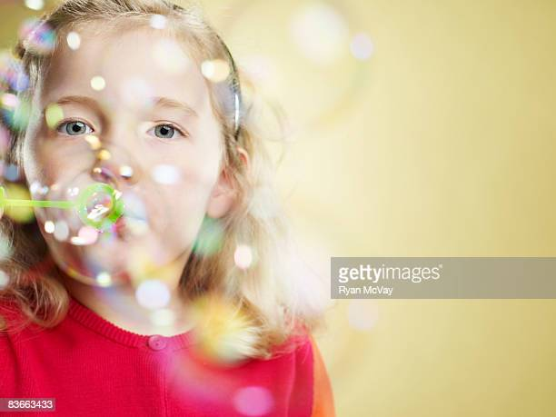 Five year old girl blowing bubbles.
