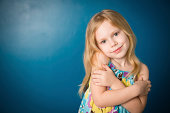 """""""Color image of a  blond-haired little girl, giving herself a hug. Includes blue background and copy space."""""""
