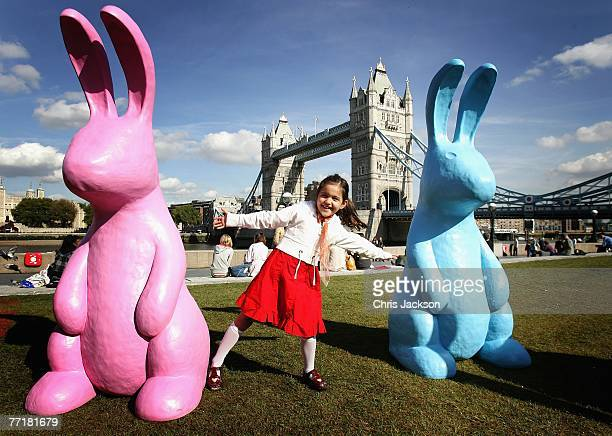 Five year old Nadia from New Zealand plays with some of the giant technicolor rabbits on the grass in front of Tower Bridge on October 4 2007 in...