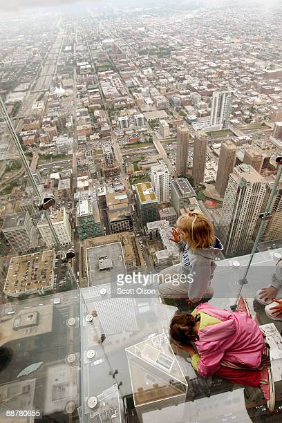 Five yearold Anna Kane and 4yearold Sophie Allaway check out the view from the Ledge a new glass cube that juts out from the 103rd floor Skydeck of...