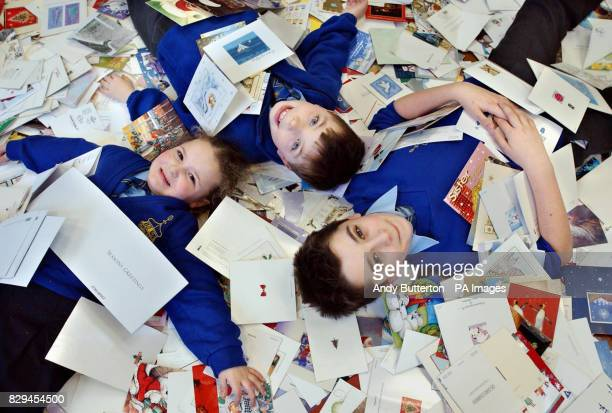 five yearold Grace Onder eight yearold Ben Wiltshire and 10 yearold Joshua Shackleton pose among some of the 336000 cards collected by pupils The...