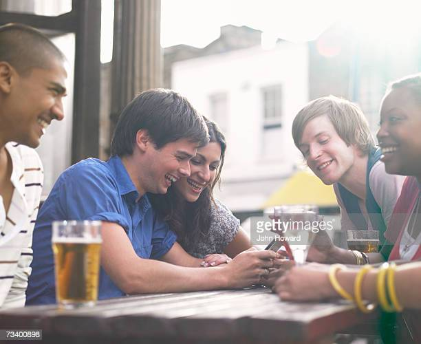 Five young adults sitting at outdoor pub table, man with mobile phone