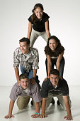 Five young friends forming pyramid, posing in studio, portrait