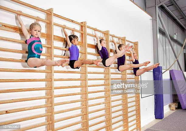 Five young gymnasts holding pose on bars