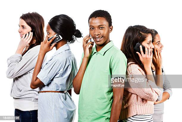 Five young people back-to-back chatting on mobile phones