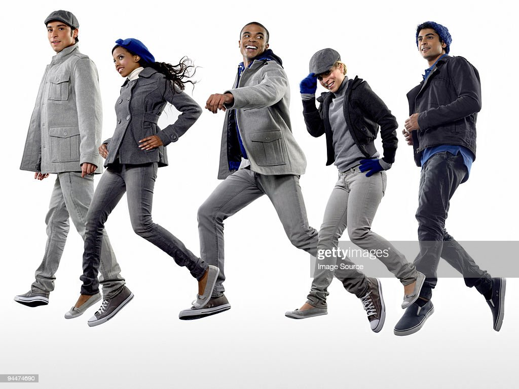 Five young people in coats jumping : Stock Photo