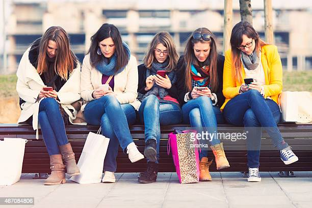 Five young women using smartphones at a mall