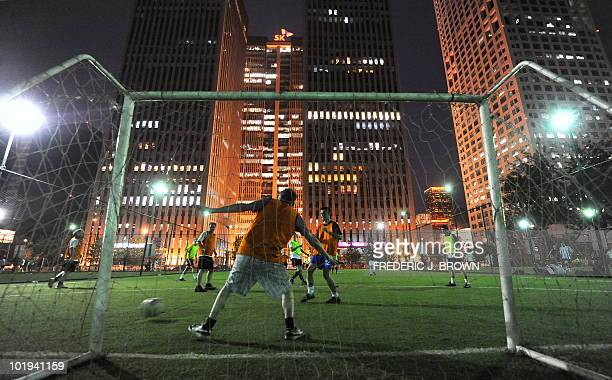 A fiveaside pickup game takes place under floodlights on an artifical grass pitch beneath office towers in Beijing on June 9 2010 World Cup fever is...
