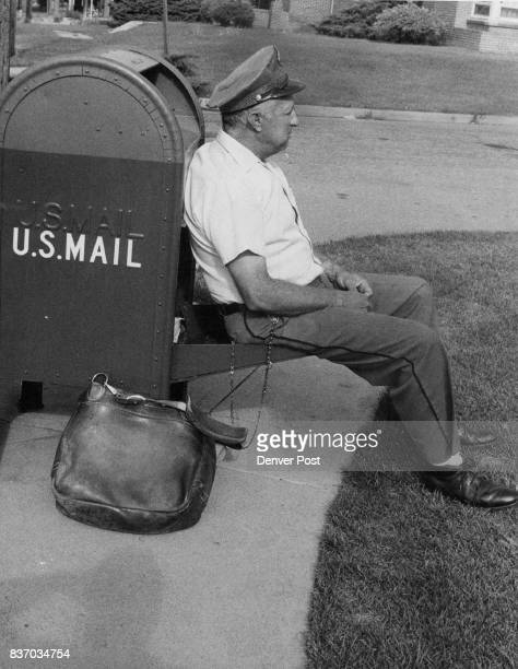 FiveDay Week Stops Swiftness Denver Postman J H O'Brien of 1925 Xanthia St relaxes on the best seat he can find at E 2nd Ave and Harrison St...