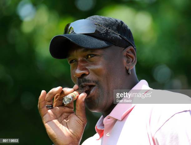 Fivetime NBA MVP Michael Jordan smokes a cigar after hitting to the seventh green during the RBC Canadian Open's Mike Weir Charity Classic ProAm at...