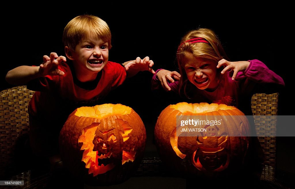 Five-year-old Aidan (L) and his seven-year-old sister Autumn pose next to their pumpkins after carving them at their home in Centreville, MD, October 23, 2012. AFP PHOTO/Jim WATSON