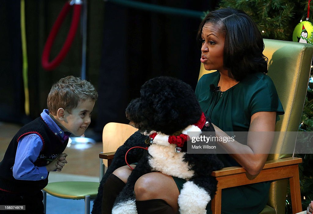 Five-year-old AJ Murray looks at the first dog, Bo, as first lady <a gi-track='captionPersonalityLinkClicked' href=/galleries/search?phrase=Michelle+Obama&family=editorial&specificpeople=2528864 ng-click='$event.stopPropagation()'>Michelle Obama</a> reads a Christmas story during a visit to Children's National Medical Center on December 14, 2012 in Washington, DC. The first lady toured the hospital before greeting 200 patients and hospital staff.