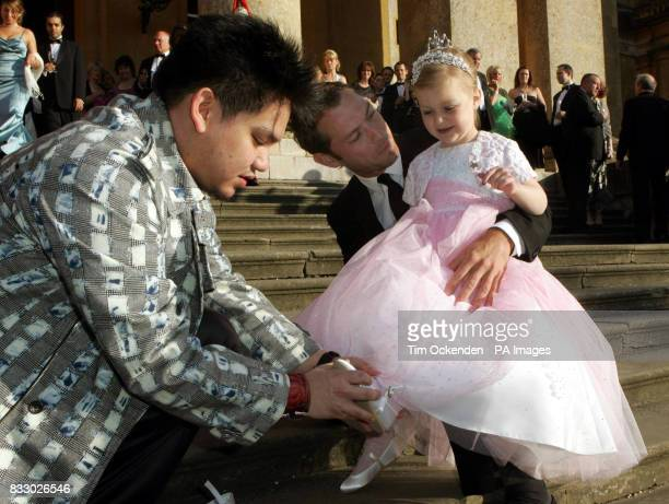 Fiveyearold Ellie Stirling sits on the lap of film star Jude Law while Prince Azim of Brunei places a pair of 'satin slippers' on her feet during the...