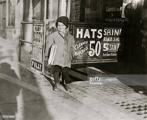 Fiveyearold Hymie Miller stands on a sidewalk where he sells newspapers after school New York New York 1924