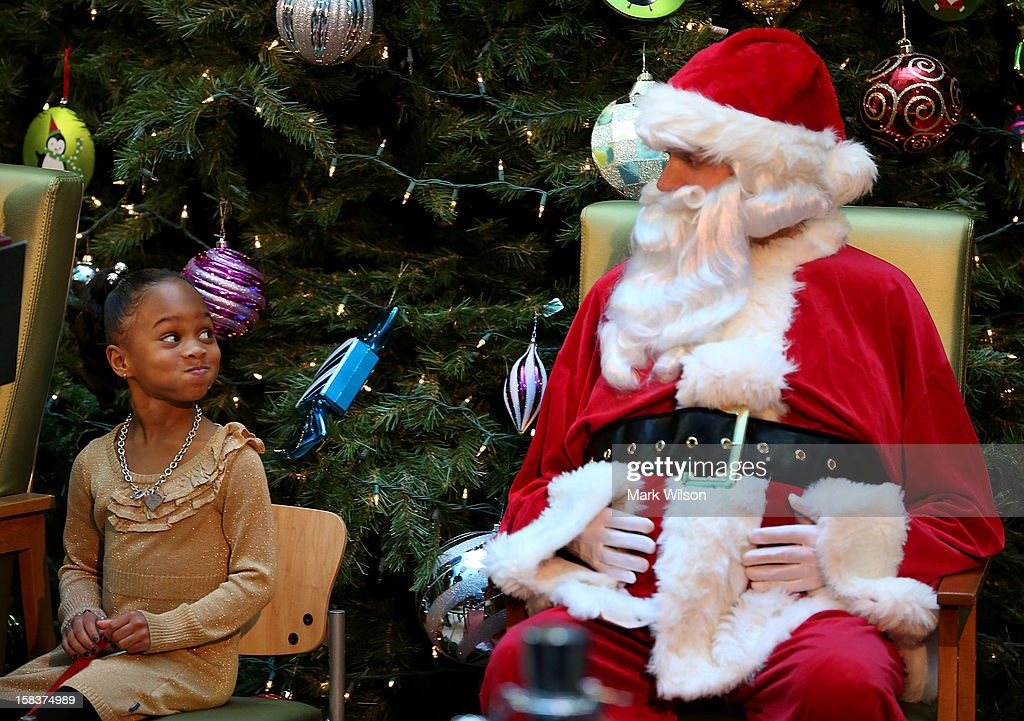 Five-year-old Jordyn Akyoko looks at a Santa Claus impersonator during a Christmas story reading by first lady Michelle Obama at Children's National Medical Center on December 14, 2012 in Washington, DC. The first lady toured the hospital before greeting 200 patients and hospital staff.