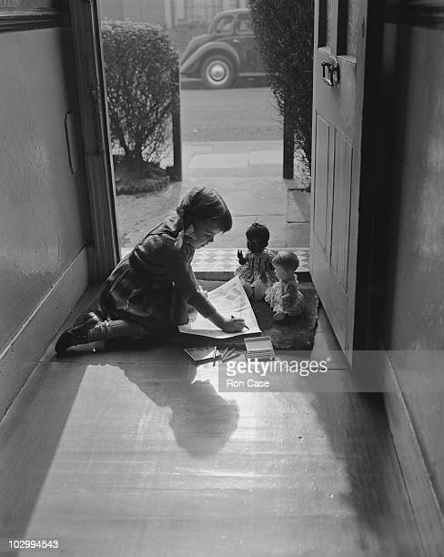 Fiveyearold Wendy Case of East London plays with her dolls in the doorway of her home 1959