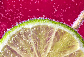 A slice of lime submerged in fizzy pink drink with bubbles.