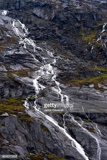 A freshwater stream cascades down a mountainside in an Arctic fjord.