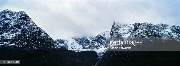 Rugged black mountain peaks shrouded in snow and ice tower above an arctic fjord.
