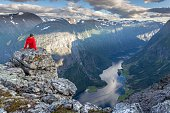 Man rests above Naeroyfjord and enjoys the view from Breiskrednosi, Norway