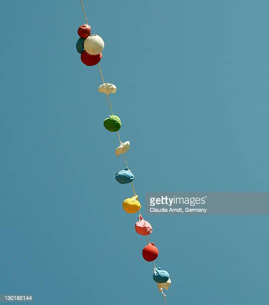 Flaccid balloons hanged under clear sky