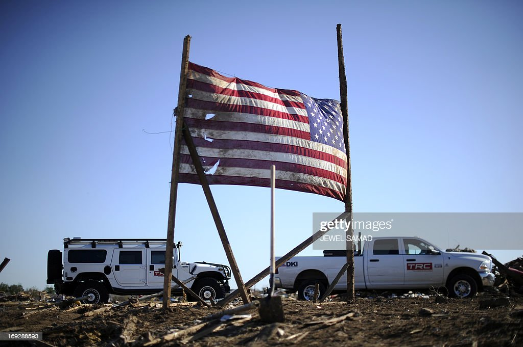 A US flag, allegedly belongs to the Plaza Towers Elementary School, is displayed amongst the debris of the tornado devastated school on May 22, 2013 in Moore, Oklahoma. Seven children died in the school during the tornado. As rescue efforts in Oklahoma wound down, residents turned to the daunting task of rebuilding a US heartland community shattered by a vast tornado that killed at least 24 people. The epic twister, two miles (three kilometers) across, flattened block after block of homes as it struck mid-afternoon on May 20, hurling cars through the air, downing power lines and setting off localized fires in a 45-minute rampage. AFP PHOTO/Jewel Samad