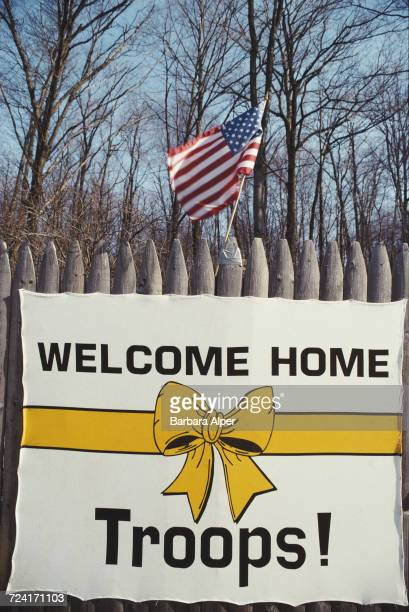 A US flag and a banner with a yellow ribbon image and reading 'Welcome Home Troops after the First Gulf War USA April 1991