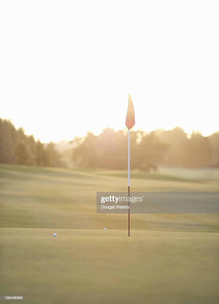 Flag and golf balls on green at sunset : Stock Photo