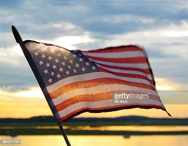 US flag at sunset by river or bay