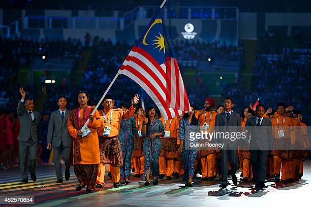 Flag bearer and Cyclist Fatehah Mustapa of Malaysia flies the flag at half mast during the Opening Ceremony for the Glasgow 2014 Commonwealth Games...