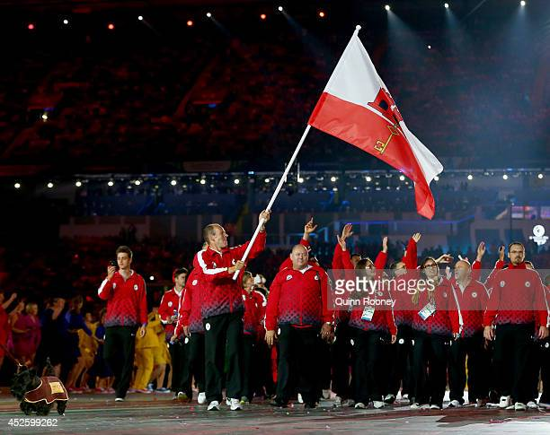 Flag bearer and Triathlete Chris Walker of Gibraltar leads his team during the Opening Ceremony for the Glasgow 2014 Commonwealth Games at Celtic...