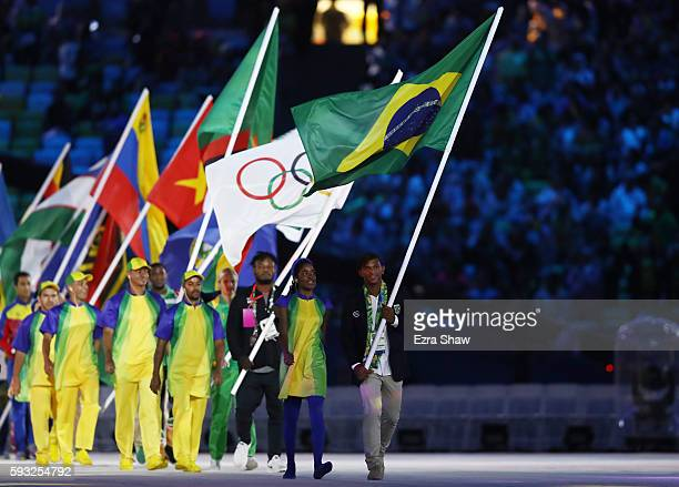 Flag bearer Isaquias Queiroz Dos Santos of Brazil walks during the 'Heroes of the Games' segment during the Closing Ceremony on Day 16 of the Rio...