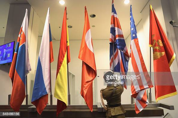 A flag bearer places the flag of the United Kingdom among flags of other NATO member states at the PGE National Stadium site of the NATO summit on...