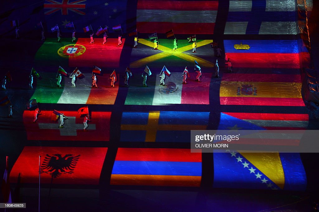Flag bearers walk over the projection of flags during the opening ceremony of the FIS World Ski Championships on February 4, 2013 in Schladming. AFP PHOTO / OLIVIER MORIN