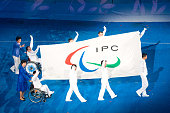 Flag bearers wave to the crowd during entrance of Athletes in the Opening Ceremony for the 2008 Paralympic Games at the National Stadium on September...